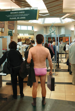 Man at airport security, having removed everything but his pink underwear and socks
